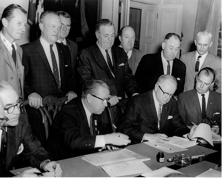 Governor Tawes signs bill with Senate president George Della, Speaker of House Perry Wilkerson, Secretary of State Lloyd Simpkins. Snowden Carter (third from left) looks on.